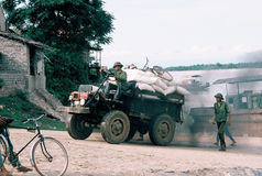 Uphill stuggle. Homemade truck leaving ferry dock with full cargo of rice, spewing exhaust, in northern Vietnam Stock Image