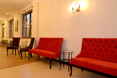 Upholstered furniture costs along a wall in the hall. Interior.  Royalty Free Stock Photos