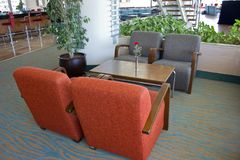 Upholstered furniture in the hotel lobby. Gray armchairs, wooden Royalty Free Stock Photos