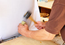 Upholsterer eliminating old staples with tool Royalty Free Stock Photos