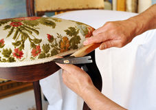 Upholsterer lining the seat of a chair Stock Photos