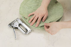 Upholstering a part of chair by staple gun Stock Photography