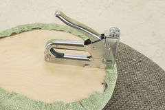 Upholstering a part of chair by staple gun Stock Photo
