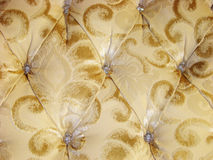 Upholstery with gold pattern. And buttons with rhinestones Royalty Free Stock Images