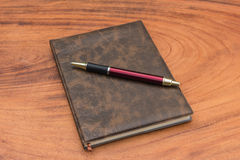 Upholstery Notebook and Pen. On wood background Stock Image