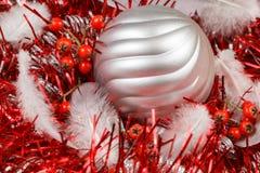Upierza, czerwone jagody i srebrzysta Bożenarodzeniowa piłka na czerwonym świecidełku Obrazy Stock