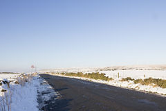Upland country road in snow with wind farm Stock Images