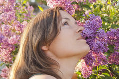 Uplifting aroma. Beautiful young woman enjoying the scent of a lilac flower Stock Photography