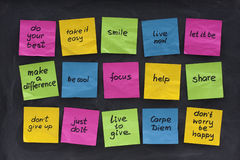 Uplifting and motivational words. Colorful sticky notes with uplifting and motivational words of wisdom posted on blackboard with eraser smudges Royalty Free Stock Photos