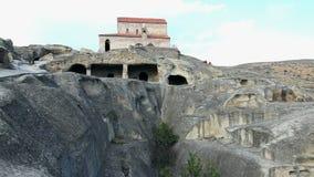 Uplistsikhe. Orthodox Church and Uplistsikhe rock cut city in Georgia stock video
