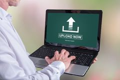 Upload concept on a laptop. Man using a laptop with upload concept on the screen Stock Photography
