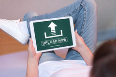 Upload concept on a tablet. Woman looking at upload concept on a tablet Royalty Free Stock Image