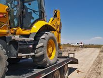 Uploaded. A construction Back Hoe loaded on to its trailer Royalty Free Stock Image