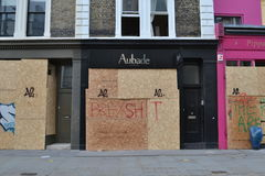 Upmarket boutiques boarded up covered graffiti Royalty Free Stock Image