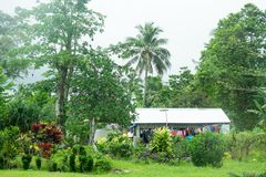 Upolu Island, Samoa - October 30, 2017: Samoan home with colorful laundry hanging outside the home, amongst green plants and trees. In garden royalty free stock photo