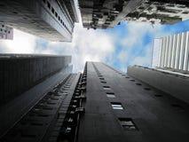 Uppåtriktad sikt av högväxta skyskrapor mot en blå himmel och moln arkivbild