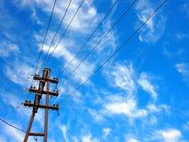 Uppåtriktad sikt på kraftledningar och elektrisk pol arkivbild