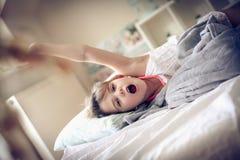 upp att vakna Unge på säng Royaltyfri Foto