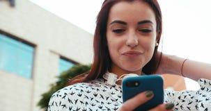 Upp ståenden av den förtjusande le brunetten som smsar och bläddrar via den utomhus- mobiltelefonen lager videofilmer