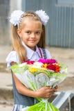 Upp ståenden av enår skolaflicka med buketten av blommor arkivbild