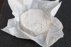 Uppackad mjuk ost för den engelska Brie på en grå färg kritiserar bakgrund Fotografering för Bildbyråer