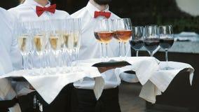 Uppassare hälsar gäster med alkoholdrycker Champagne rött vitt vin på magasin arkivfilmer