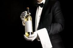 Uppassare i smokingen som rymmer en bottel av vitt vin Arkivfoton