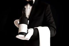Uppassare i smokingen som rymmer en flaska av rött vin Arkivbild