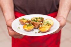 Uppassare med en platta av potatisar Arkivfoto