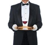 Uppassare med exponeringsglas av rött vin på magasinet royaltyfri bild