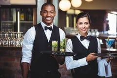 Uppassare och servitris som rymmer ett portionmagasin med exponeringsglas av coctailen royaltyfri fotografi