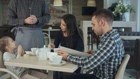 Uppassare som ger menyn till den lyckliga familjen på kafét Fader som konsulterar med honom royaltyfria foton