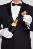 Uppassare som öppnar en buteljera av champagne Royaltyfri Fotografi