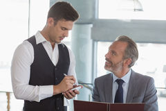 Uppassare som tar beställningen från en affärsman Arkivfoton