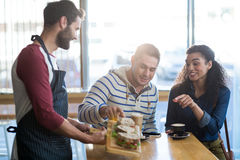 Uppassare som tjänar som en platta av smörgåsen till kunden royaltyfria foton