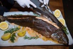 Uppassarehänderna i vita handskar som klipper fisken i restaurangen Royaltyfria Bilder