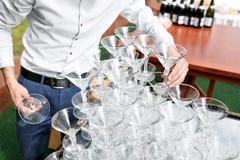Uppassaren bygger en pyramid av exponeringsglas för champagne Arkivfoton