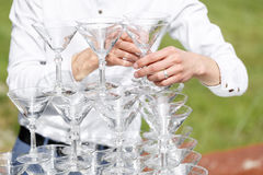 Uppassaren bygger en pyramid av exponeringsglas för champagne Arkivfoto