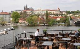 Uppassaren gör ren tabeller på en utomhus- restaurang på flodstranden av Vltava i Prague, med den Prague slotten i bakgrunden Arkivfoto