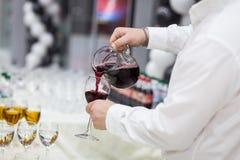 Uppassaren häller champagne in i ett exponeringsglas Tomma exponeringsglas på whien Arkivbild