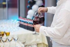 Uppassaren häller champagne in i ett exponeringsglas Tomma exponeringsglas på whien Royaltyfria Foton