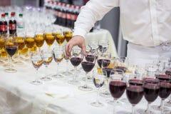 Uppassaren häller champagne in i ett exponeringsglas Tomma exponeringsglas på whien Royaltyfria Bilder