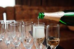 Uppassaren häller champagne i exponeringsglas, lyxig händelse arkivbilder