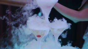 Uppassaren häller champagne in i exponeringsglas med gröna körsbär och ånga av torr is Champagneglidbana Pyramid eller springbrun lager videofilmer