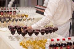 Uppassaren häller vin in i ett exponeringsglas exponeringsglas på den vita tabellen, A Royaltyfri Foto