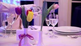Uppassaren häller vitt vin in i ett exponeringsglas i en hemtrevlig restaurang stock video