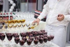 Uppassaren häller whisky in i ett exponeringsglas exponeringsglas på den vita tablen Royaltyfria Foton