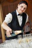 Uppassaren häller ett exponeringsglas av champagne Arkivbilder