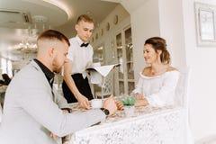 Uppassaren kom med koppen kaffe för härliga par i ett kafé Royaltyfri Bild