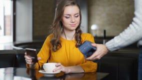 Uppassaren kommer med damSTIFTblocket för kontakt mindre betalning, kvinnalönräkning med telefonen stock video